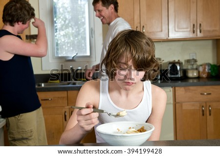 Boy eating breakfast with brother and father in background - candid shoot