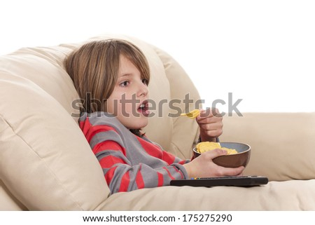 boy eating chips and watching television - stock photo