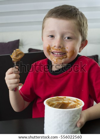Boy eating chocolate in spoon.