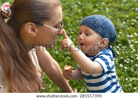 Boy eating ice-cream and playing with his mom - stock photo