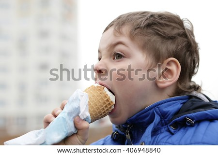 Boy eating ice cream outdoor in spring
