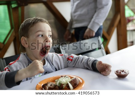 Boy eating kebab with onions in the cafe