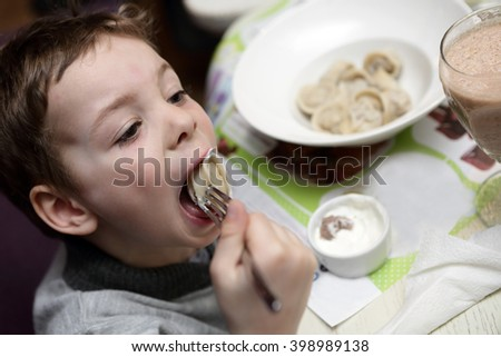 Boy eating meat dumplings in a cafe - stock photo