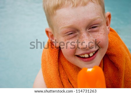 Boy eating orange popsicle by a swimming pool