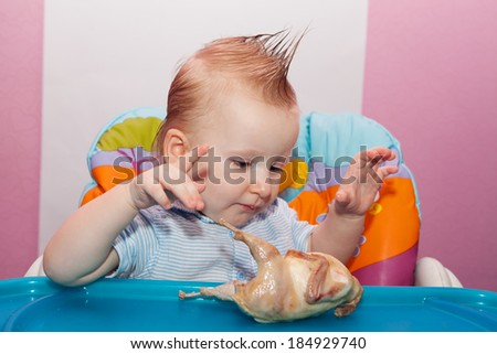 Boy eating roasted chicken leg  - stock photo