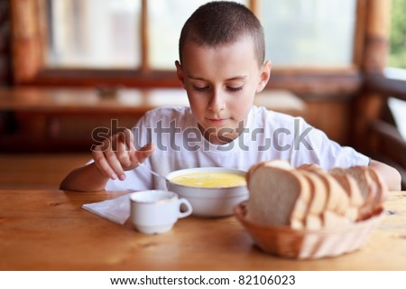 Boy eating soup for dinner in a rustic restaurant outdoor - stock photo