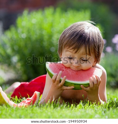 Boy, eating watermelon in the garden, summertime - stock photo