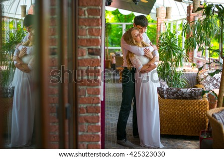 Boy embraces from behind his girl - stock photo