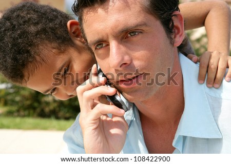 boy embracing his father while he is talking on his cell - stock photo