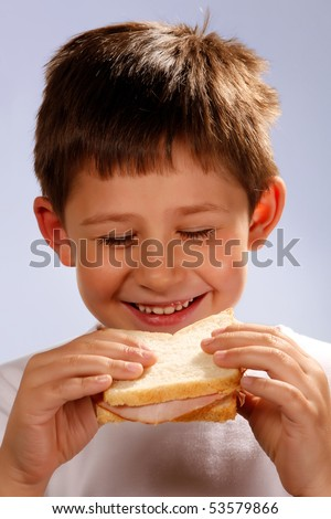 boy enjoying eating sandwich - stock photo