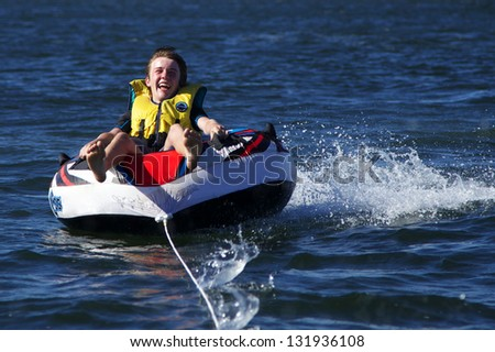 Boy Enjoying Skiing on Inflatable Behind Speed Boat - stock photo