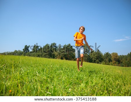 Boy enjoying summertime running through a sunny meadow in a summer forest - stock photo