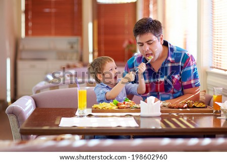 boy feeding father in restaurant - stock photo