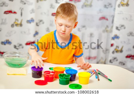 Boy finger paints on paper at his room - stock photo