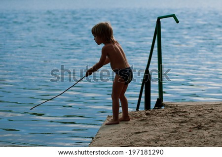 Boy fishes on the bank of small river. branch instead hook - stock photo