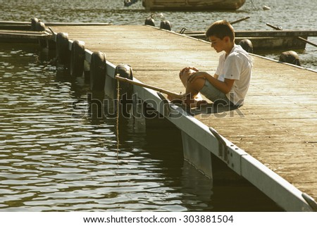 boy fishing in the river - stock photo