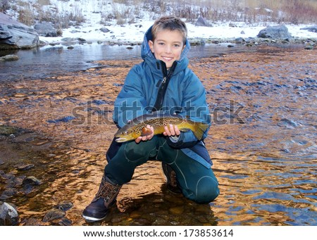 Boy fishing - young man with a nice fish (Brown Trout) caught fly fishing in a river on a cold winter day  - stock photo