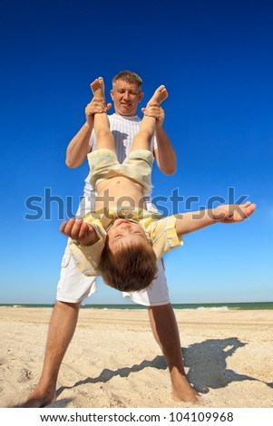 Boy flying on his parent 's hands at beach - stock photo