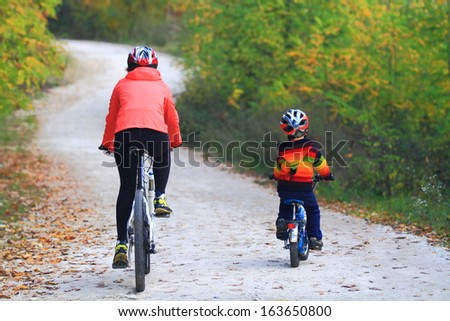 Boy followed by his mother during bike ride in autumn forest - stock photo