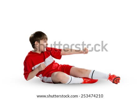 Boy football player in red uniform against white background - stock photo