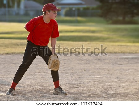 Boy getting ready to pitch, backlit - stock photo