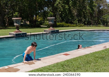 Boy Girl Pool Summer Boy girl swim pool home summer playing holidays - stock photo