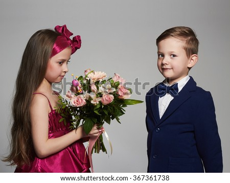 boy gives a girl flowers.little beautiful couple.kids love,valentine - stock photo