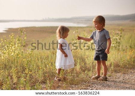 boy giving bouquet of spring flowers to happy girl - stock photo