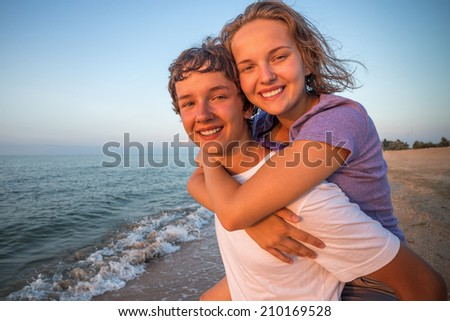 Boy giving piggyback ride to girlfriend by the sea