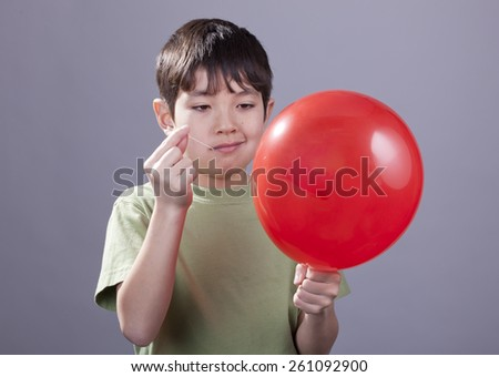 Boy going to pop balloon. - stock photo