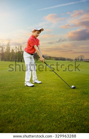 Boy golf player hitting by iron from fairway - stock photo