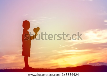 boy hands holding hearts silhouette - stock photo