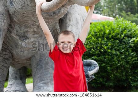 Boy hanging on an elephant tusks sculpture. Amusement park. - stock photo
