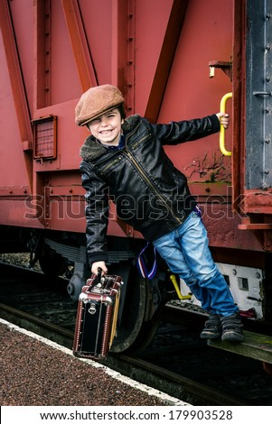 boy hanging on the side of a train, with instagram style effect added. - stock photo