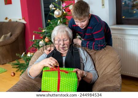 boy has a christmas present for his grandma - stock photo