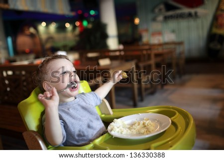 Boy has a lunch in a high chair at a restaurant - stock photo