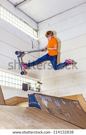 boy has fun riding his scooter in the skate hall - stock photo