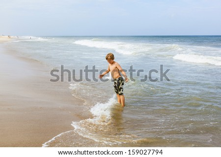 boy has fun standing in the ocean in the stormy beach