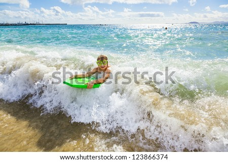 boy has fun with the surfboard at the beach - stock photo