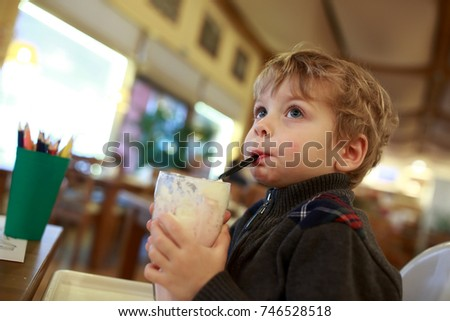 Boy has milkshake at table in cafe