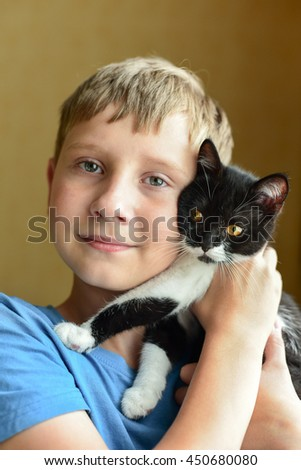 boy has picked up a little kitten - stock photo