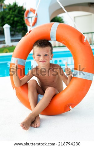 Boy have fun by posing with lifebuoy next to waterpool