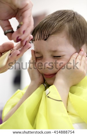Boy having a haircut at the barbershop
