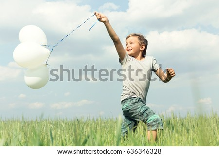 Boy having fun with his balloons in the middle of nature