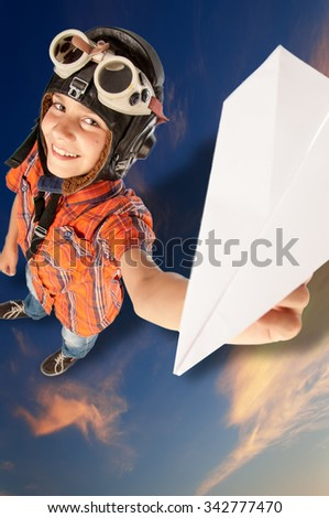 Boy headset pilot with glasses and a paper airplane - stock photo