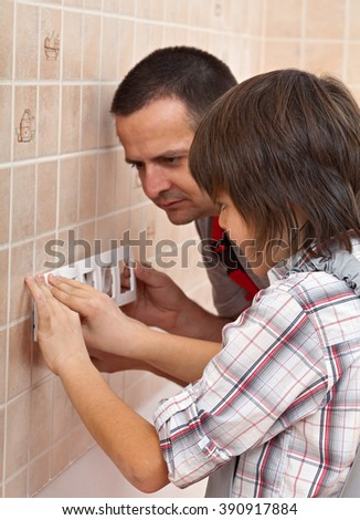 Boy helping his father install the front panel of electrical wall fixture - snapping it into place - stock photo