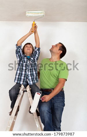 Boy helping his father to paint the room - sitting on top of ladder