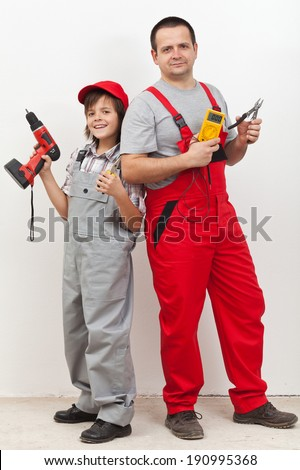 Boy helping his father with some electrical work - standing back to back with tools - stock photo