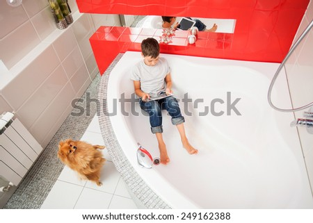 Boy hiding in the bathroom, playing in tablet. Computer Addiction, gambling, lie - stock photo