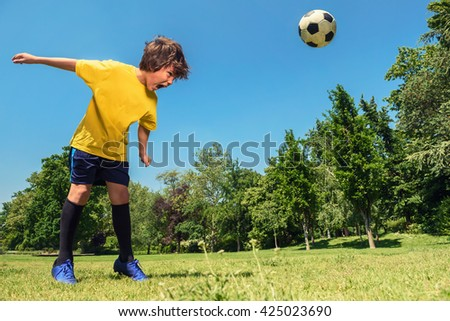 Boy Hits a Soccer Ball With Head in the Park - stock photo